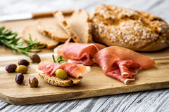 Prosciutto with olives. On wooden background Stock Photos