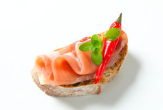 Prosciutto open faced sandwich. Garnished with red chili peppers Stock Photo