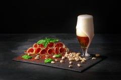 Prosciutto ou balyk curado com pistaches, um espinafre e uma cerveja clara com espuma em um fundo preto Copie o espaço Pistaches  fotos de stock royalty free