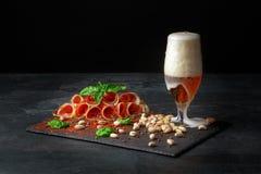 Prosciutto ou balyk curado com pistaches, um espinafre e uma cerveja clara com espuma em um fundo preto Copie o espaço Pistaches  fotos de stock
