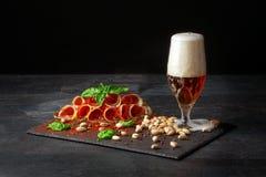 Prosciutto ou balyk curado com pistaches, um espinafre e uma cerveja clara com espuma em um fundo preto Copie o espaço Pistaches  fotografia de stock