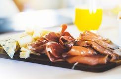 Prosciutto, parmesan na drewnianej desce na kuchennym stole, plamy pojęcie, hiszpański śniadanie z serrano jamon i Gorgonzola ser obrazy stock
