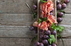 Prosciutto with parsley and grapes on a old wooden table. Stock Photos
