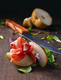 Prosciutto with pear on a wooden table Royalty Free Stock Image