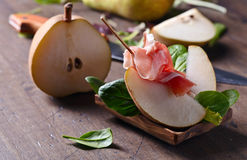 Prosciutto with pear on a wooden table Stock Photo