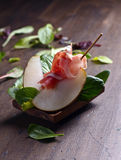 Prosciutto with pear on a wooden table Royalty Free Stock Photo