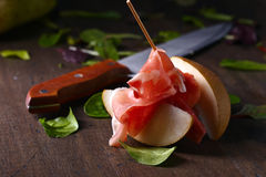 Prosciutto with pear on a wooden table Royalty Free Stock Images