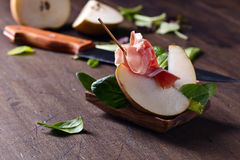 Prosciutto with pear on a wooden table Royalty Free Stock Photography