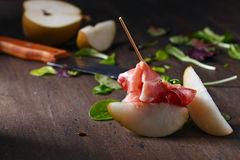 Prosciutto with pear on a wooden table Stock Images