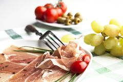 Prosciutto plate. Delicious prosciutto plate with olives, tomatos and grapes royalty free stock photos