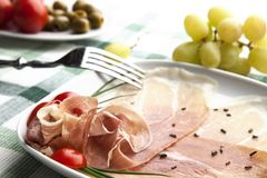 Prosciutto plate. Delicious prosciutto plate with olives, tomatos, grapes and a fork Stock Photo