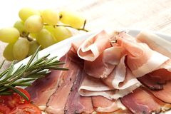 Prosciutto plate. Delicious prosciutto plate with tomatos, grapes and rosemary Stock Images