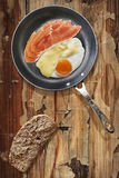 Prosciutto Rashers With Fried Egg In Frying Pan With Slice Of Brown Bread Set On Old Cracked Wooden Garden Table Royalty Free Stock Image