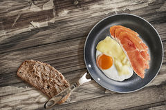 Prosciutto Rashers With Fried Egg In Frying Pan With Slice Of Brown Bread Set On Old Cracked Wooden Garden Table. Fried Sunny side up egg, with Edam cheese, and Royalty Free Stock Photography