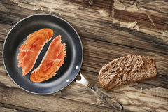 Prosciutto Rashers in Teflon Frying Pan with Bread Slice on very Stock Images