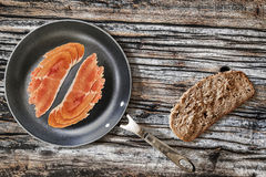 Prosciutto Rashers In Teflon Frying Pan And Slice Of Brown Bread Set On Old Cracked Wooden Picnic Table Stock Photography