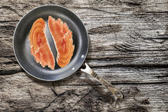 Prosciutto Rashers In Teflon Frying Pan Set On Old Cracked Wooden Picnic Table Stock Image