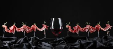 Prosciutto with rosemary and glass of red wine on a black backgr Royalty Free Stock Image
