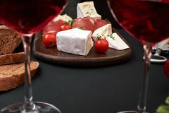 Prosciutto, salame, fatias do baguette, tomates e placa de madeira rústica do nutson, dois vidros do vinho tinto sobre o preto Foto de Stock Royalty Free