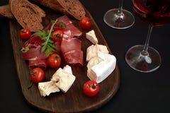 Prosciutto, salame, fatias do baguette, tomates e placa de madeira rústica do nutson, dois vidros do vinho tinto sobre o preto Imagem de Stock