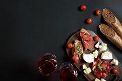 Prosciutto, salame, fatias do baguette, tomates e placa de madeira rústica do nutson, dois vidros do vinho tinto sobre o preto Foto de Stock