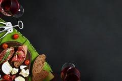 Prosciutto, salame, fatias do baguette, tomates e placa de madeira rústica do nutson, dois vidros do vinho tinto sobre o preto Imagens de Stock