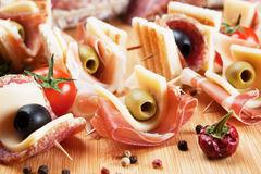Prosciutto and salami canape. Prosciutto, salami, cheese and olive canape appetizer on wooden board Royalty Free Stock Photography