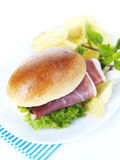 Prosciutto sandwich. A sandwich made of prosciutto,lettuce,pesto sauce and a small brioche bread served with potato chips and basil leaves on a white plate and a stock photography
