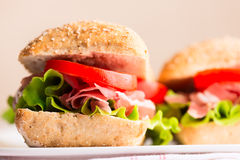 Prosciutto sandwich with tomato and arugula on plate Stock Photo