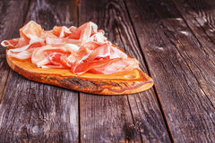 Prosciutto served on a olive cutting board Royalty Free Stock Images