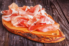 Prosciutto served on a olive cutting board Royalty Free Stock Image