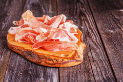 Prosciutto served on a olive cutting board Royalty Free Stock Photos