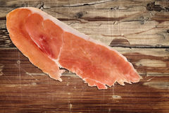 Prosciutto Slice on Old Wooden Background Royalty Free Stock Photo