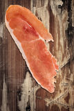 Prosciutto Slice on Old Wooden Background Stock Photography