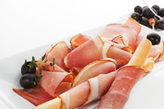 Prosciutto slices with black olives. Royalty Free Stock Images