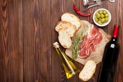 Prosciutto, vin, oliv, parmesan och olivolja arkivfoto
