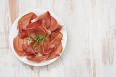 Prosciutto on white plate on white background Stock Photos