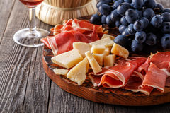 Prosciutto, wine, grape, parmesan on wooden table. Royalty Free Stock Photo
