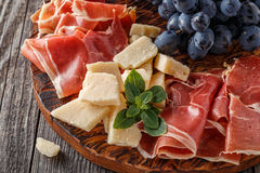 Prosciutto, wine, grape, parmesan on wooden table. Stock Photography