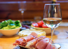 Prosciutto and wine. Sliced prosciutto with a glass of wine, cheese and vegetables in the background Royalty Free Stock Photo
