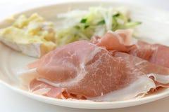Prosciuttoskinka med ost och sallad i vit bakgrund Arkivfoton
