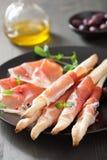 Prosciuttoskinka och grissini. italiensk antipasto Fotografering för Bildbyråer
