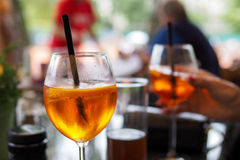 Prosecco wine and aperol. Glasses of Prosecco wine and aperol on table with people in background, outdoor scene royalty free stock photography