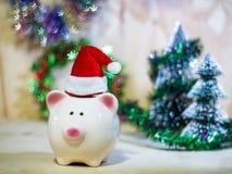 Prosiątka oszczędzania bank z Santa kapeluszem na drewnianej podłoga obrazy stock