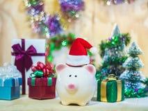 Prosiątka oszczędzania bank z Santa kapeluszem na drewnianej podłoga fotografia royalty free