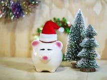 Prosiątka oszczędzania bank z Santa kapeluszem na drewnianej podłoga obraz stock