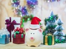 Prosiątka oszczędzania bank z Santa kapeluszem na drewnianej podłoga zdjęcia stock