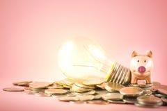 Prosiątko żarówka lub bank jesteśmy stertą na monetach wypiętrzamy dla ratować pieniądze pojęcie Kreatywnie pomysł pieniężny obraz stock