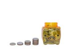 Prosiątko bank i sterty moneta na odosobnionym tle Obraz Royalty Free
