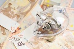 Prosiątko bank, monety i euro rachunki, banknotów czarny kalkulatora pojęcia pieniądze oszczędzanie Banknotu zbliżenie Zdjęcia Royalty Free